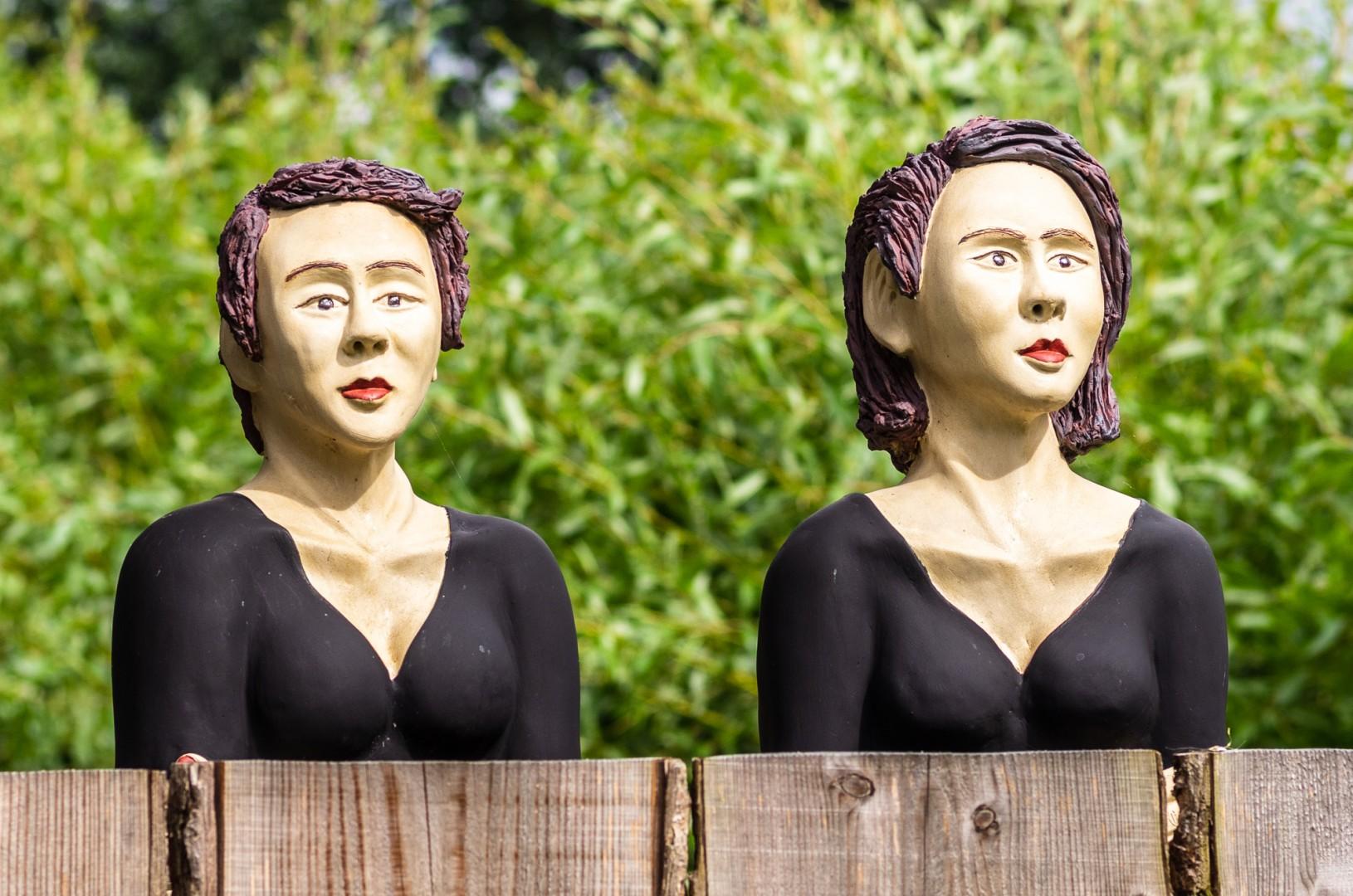 2 Keramikbüsten hinter Lärchenholzzaun, Höhe ca. 45 cm, frostfest